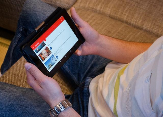 mužské ruky držia tablet, pozerať Youtube