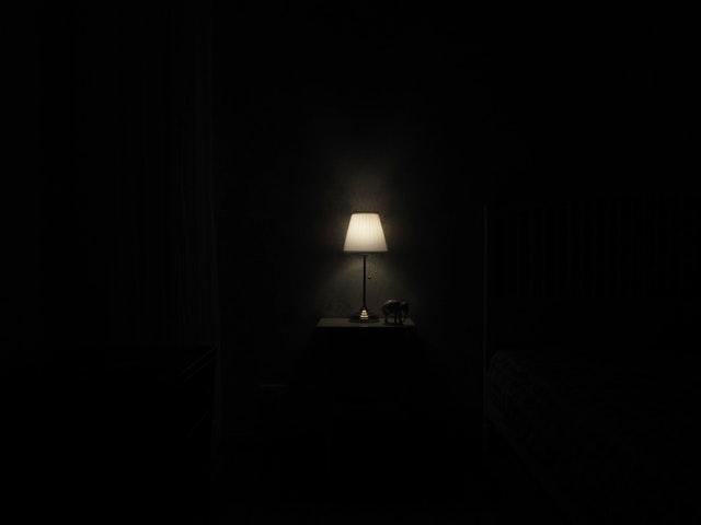 Zasvietená malá lampa v tmavej miestnosti.jpg