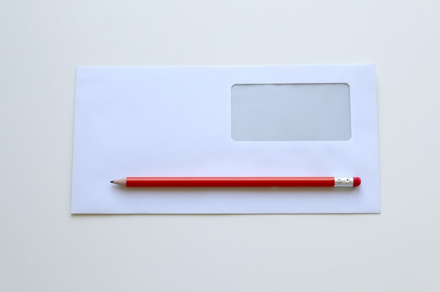 Biela obálka s fóliou a červené pero.jpg